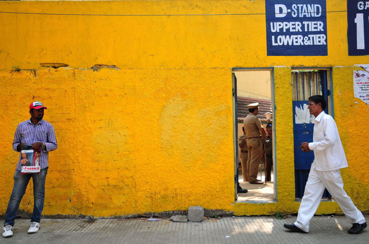Indian police stand inside a stadium before a cricket match between Australia and India as fans walk past in Chennai on February 22, 2013.  Australian authorities said they plan to play the second Test in Hyderabad as scheduled next week despite deadly bomb attacks in the city on the eve of the series opener. The twin blasts on February 21, killed at least 14 people and wounded dozens more in the southern Indian city, raising questions over whether Australia would play the second Test starting on March 2. AFP PHOTO/ STR        (Photo credit should read STRDEL/AFP/Getty Images)