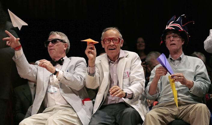 CORRECTS TO REFLECT THAT KIRSHNER IS NOT A NOBEL LAUREATE, ADDS HIS CURRENT TITLE - Harvard University Clowes Professor of Science Robert Kirshner, left, along with Nobel laureates Dudley Herschbach, center, and Rich Roberts, fire paper airplanes back at the audience during a performance at the Ig Nobel Prize ceremony at Harvard University, in Cambridge, Mass., Thursday, Sept. 20, 2012. The Ig Nobel prize is an award handed out by the Annals of Improbable Research magazine for silly sounding scientific discoveries that often have surprisingly practical applications.(AP Photo/Charles Krupa)