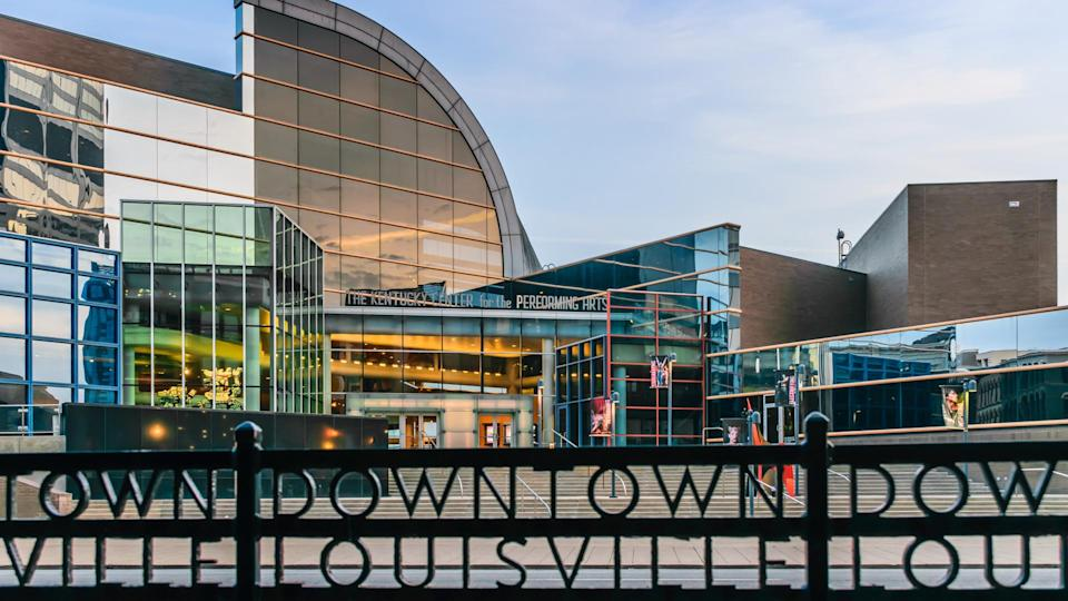 """Louisville, Kentucky, USA - March 27th 2016: Kentucky Center for the Performing Arts building in Louisville Kentucky with rod iron fence which states """"Downtown Louisville"""" in foreground."""
