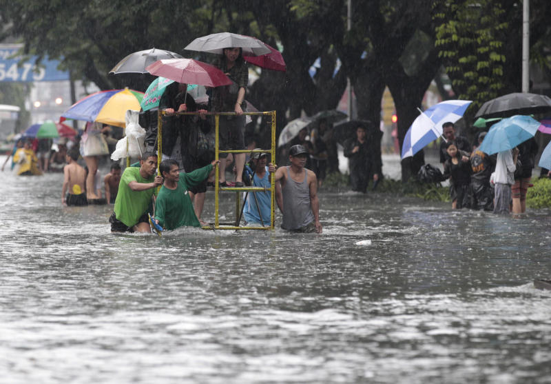 Office workers stand on top of a rolling scaffolding as they cross a flooded street at the financial district of Makati, south of Manila, Philippines on Tuesday, Aug. 20, 2013. Flooding caused by some of the Philippines' heaviest rains on record submerged more than half the capital Tuesday, turning roads into rivers and trapping tens of thousands of people in homes and shelters. The government suspended all work except rescues and disaster response for a second day. (AP Photo/Aaron Favila)