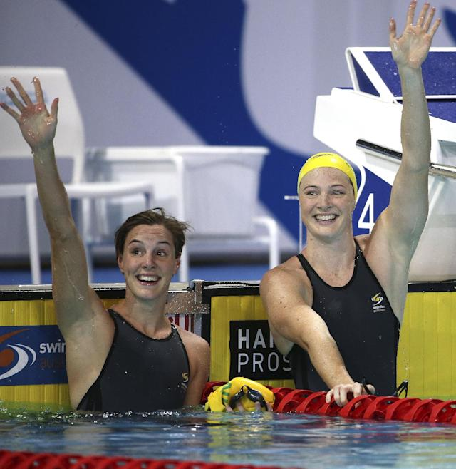 Cate Campbell of Australia right, and sister Bronte wave to the crowd after Cate won their women's 50m freestyle final at the Pan Pacific swimming championships in Gold Coast, Australia, Sunday, Aug. 24, 2014. (AP Photo/Rick Rycroft)