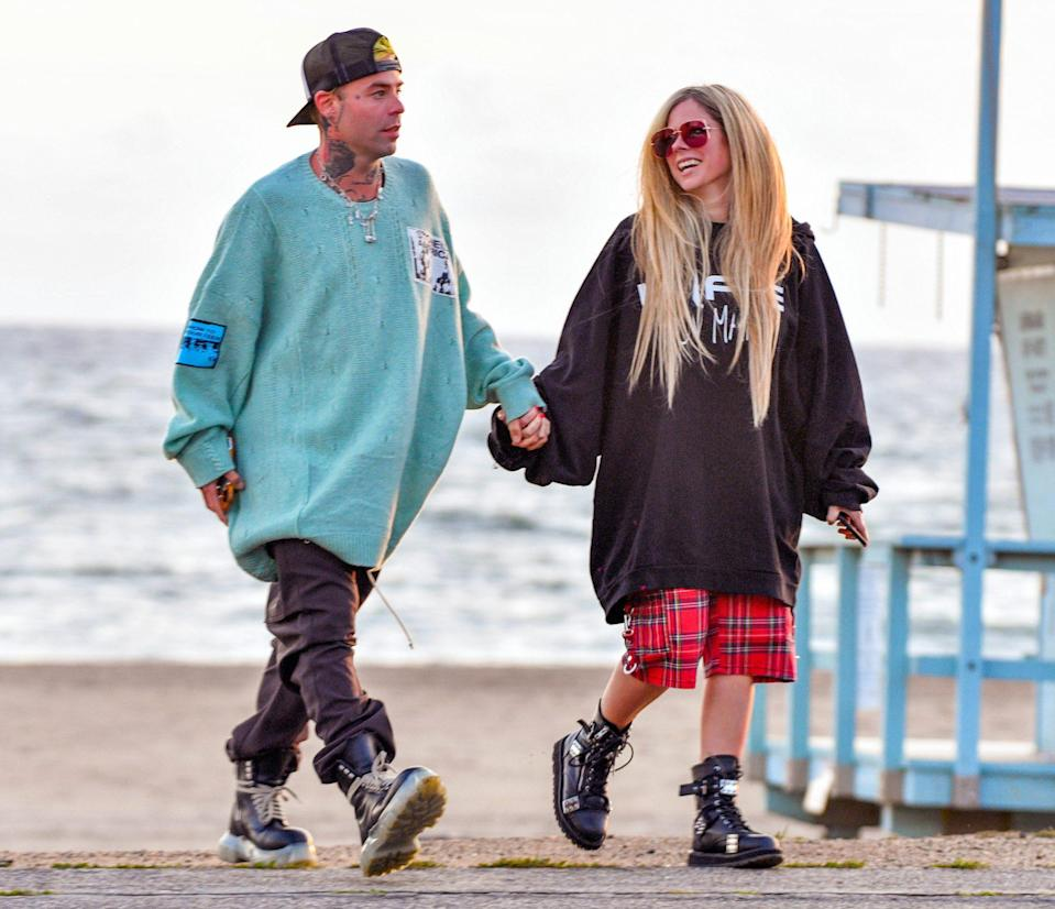 <p>Mod Sun and Avril Lavigne walk hand-in-hand along the beach in Santa Monica on Thursday.</p>