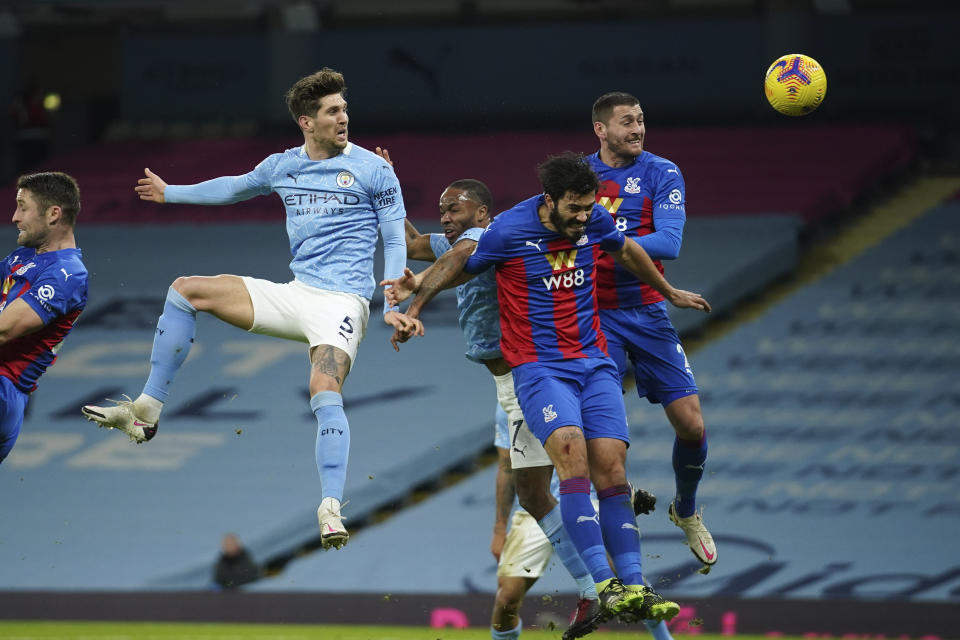 Manchester City's John Stones, centre left, heads the ball to score his side's opening goal during an English Premier League soccer match between Manchester City and Crystal Palace at the Etihad Stadium in Manchester, England, Sunday Jan.17, 2021. (AP Photo/Dave Thompson, Pool)