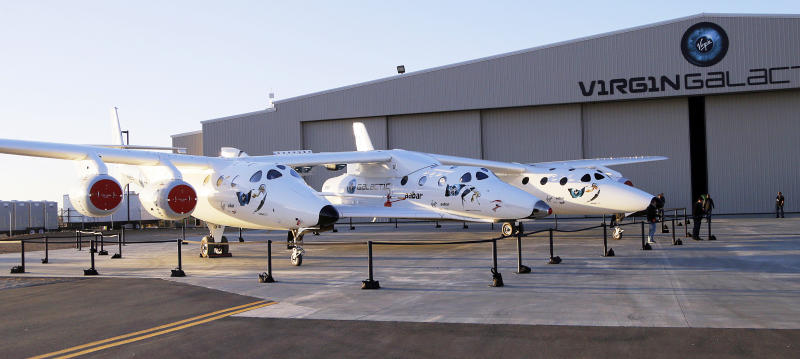 FILE - In this Sept. 25, 2013, file photo, the first SpaceShipTwo is seen suspended at center beneath its twin-fuselage mother ship at the Virgin Galactic hangar at Mojave Air and Space Port in Mojave, Calif. Boeing plans to invest $20 million in Virgin Galactic as the space tourism company nears its goal of launching passengers on suborbital flights. The companies announced the investment Tuesday, Oct. 8, 2019, saying they will work together on broadening commercial access to space and transforming global travel technologies. Virgin Galactic has conducted successful test flights of its winged rocket ship at Mojave, California, and is preparing to begin operations at Spaceport America in New Mexico. (AP Photo/Reed Saxon, File)