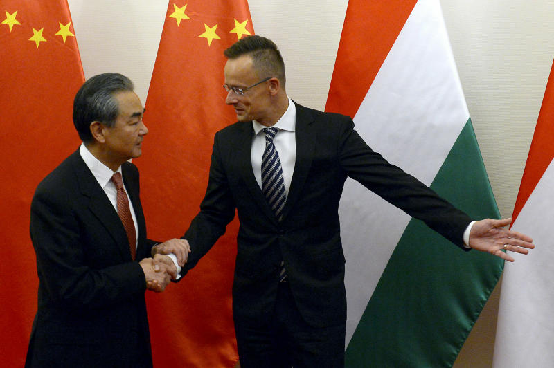 Chinese Foreign Minister Wang Yi, left, is guided by Hungarian Minister of Foreign Affairs and Trade Peter Szijjarto during their meeting in the latter's office in Budapest, Hungary, Friday, July 12, 2019. (Lajos Soos/MTI via AP)
