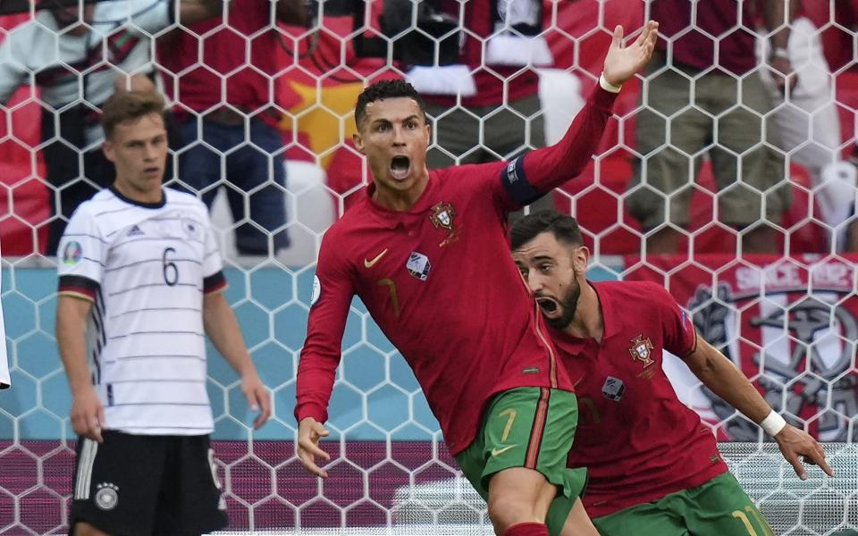 Portugal's Cristiano Ronaldo celebrates beside Germany's Joshua Kimmich, left, after scoring the opening goal during the Euro 2020 soccer championship group F match between Portugal and Germany in Munich, Saturday, June 19, 2021. (AP Photo/Matthias Schrader, Pool)