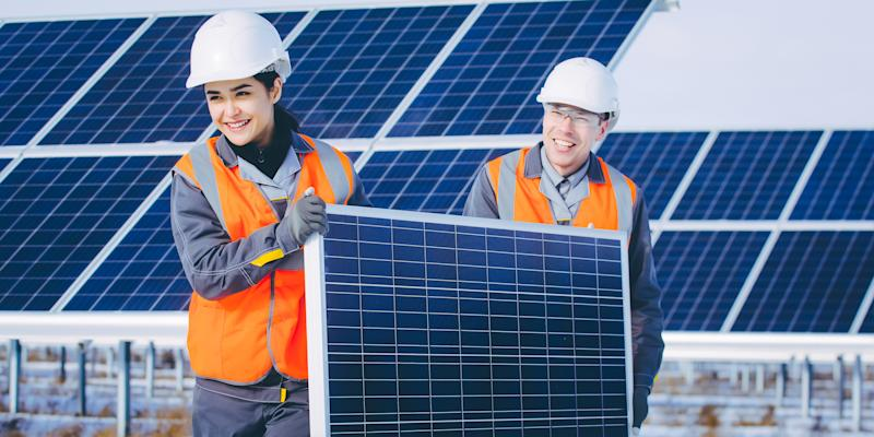 Two people carrying a solar panel with a solar farm in the background.