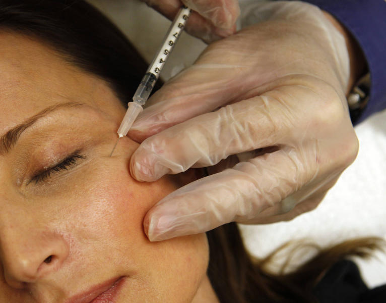 In this June 5, 2009, photo a woman has Botox injected at Reveal in Arlington, Va. AbbVie is buying Botox maker Allergan in a cash-and-stock deal the drugmakers value at around $63 billion. The maker of the blockbuster immune disorder treatment Humira said Tuesday, June 25, 2019, that it will pay $120.30 in cash and a portion of AbbVie stock for each Allergan share. (AP Photo/Jacquelyn Martin, File)