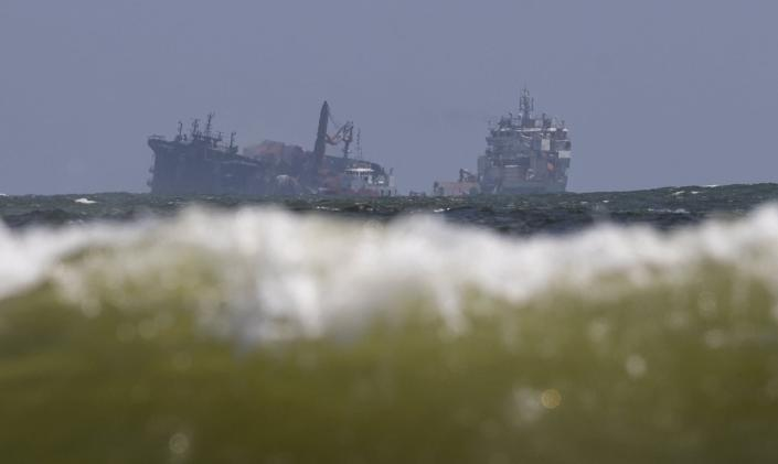 The MV X-Press Pearl, left, is pulled by a navel vessel at Kapungoda, where it is anchored off Colombo port on the outskirts of Colombo, Sri Lanka, Wednesday, June 2, 2021. Salvage experts were attempting to tow the fire-stricken container ship that had been loaded with chemicals into the deep sea as the vessel started to sink Wednesday off Sri Lanka's main port, officials said. Water submerged the MV X-Press Pearl's quarterdeck a day after firefighters extinguished a blaze that had been burning for 12 days. (AP Photo/Eranga Jayawardena)