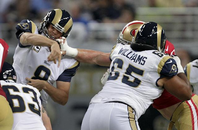 St. Louis Rams quarterback Sam Bradford, left, has his face mask grabbed by San Francisco 49ers defensive tackle Justin Smith after throwing a pass while Rams offensive tackle Chris Williams (65) gets in on the play during the first quarter of an NFL football game Thursday, Sept. 26, 2013, in St. Louis. (AP Photo/Tom Gannam)