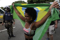 A demonstrator with a Brazilian flag protests the lockdown on the first day it goes into effect to curb the spread of COVID-19 in Brasilia, Brazil, Monday, March. 1, 2021. It's the second lockdown since the start of the pandemic one year ago. (AP Photo/Eraldo Peres)