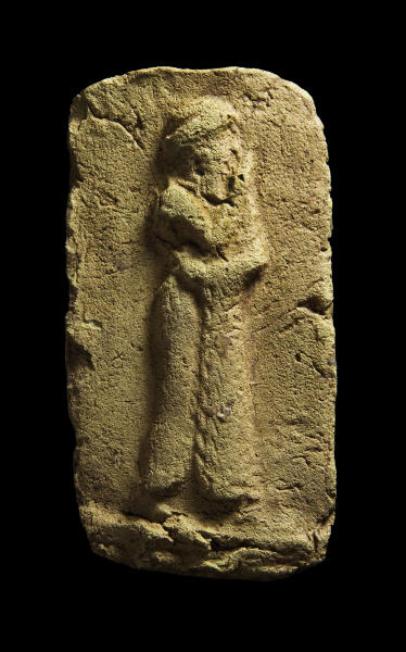 This photo taken on April 1, 2013 provided by Manchester University archaeologist Stuart Campbell shows a clay plaque, which shows a worshipper approaching a sacred place. He is wearing a long robe with fringe down the front opening, found during an excavation Tell Khaiber, Iraq. A British archaeologist says he and his colleagues have unearthed a huge, rare complex near the ancient city of Ur in southern Iraq, home of the biblical Abraham. Stuart Campbell of Manchester University's Archaeology Department says it goes back about 4,000 years, around the time Abraham would have lived there. It's believed to be an administrative center for Ur. (AP Photo/Stuart Campbell)