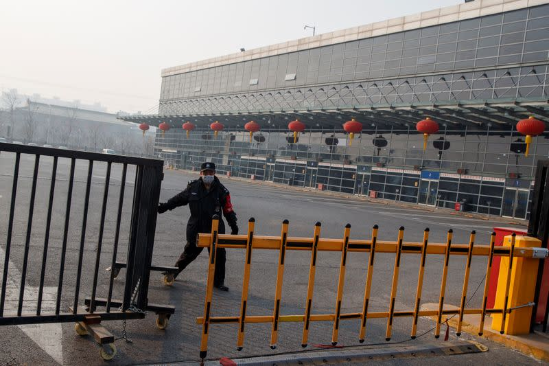 A security guard closes a gate at the Sihui Long Distance Bus Station in Beijing after the city has stoped inter-province buses services as the country is hit by an outbreak of the new coronavirus