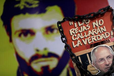 """A man holds a sign with a portrait of opposition leader Antonio Ledezma in front of a wall with a portrait of opposition leader Leopoldo Lopez during a news conference at the Venezuelan coalition of opposition parties (MUD) headquarters in Caracas, Venezuela August 1, 2017. The sign reads """"The bars will not shut the truth"""". REUTERS/Ueslei Marcelino"""
