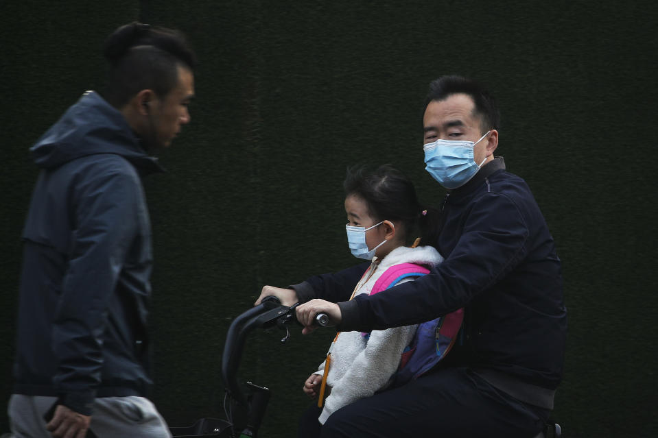 A man and a child, both wearing face masks to help curb the spread of the coronavirus ride on an electric-powered scooter in Beijing, Monday, Oct. 26, 2020. Schools and kindergartens have been suspended and communities are on lockdown in Kashgar, a city in China's northwest Xinjiang region, after more than 130 asymptomatic cases of the coronavirus were discovered. (AP Photo/Andy Wong)