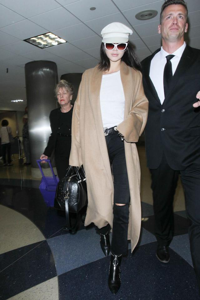 <p>In a white t-shirt under aloose-fittingcamel overcoatand black skinny jeans with studded ankle boots, a white newsboy hat, cateye sunglasses and a black leather bowler bag while arriving at the Los Angeles International Airport.</p>