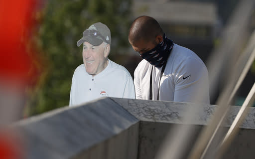 A Denver Broncos employee puts up a cutout of Fred Fleming, the team's long-time handler of players, before drills at the team's NFL football training camp Friday, Aug. 14, 2020, in Englewood, Colo. Fleming is not allowed at practices this year because of the new coronavirus. (AP Photo/David Zalubowski)