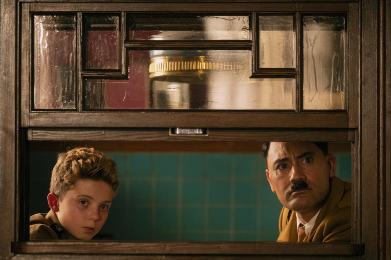 """This image released by Fox Searchlight Pictures shows, from left, Roman Griffin Davis and Taika Waititi in a scene from the WWII satirical film """"Jojo Rabbit."""" (Kimberley French/Fox Searchlight Pictures via AP)"""