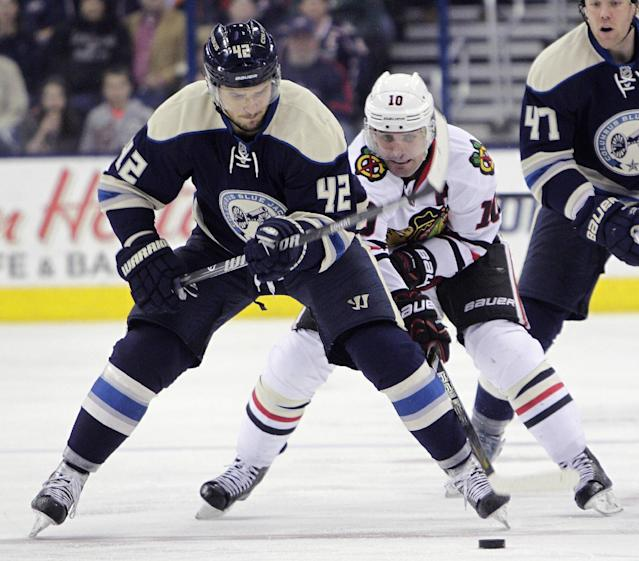 Chicago Blackhawks' Patrick Sharp (10) tries to steal the puck from Columbus Blue Jackets' Artem Anisimov, of Russia, during the third period of an NHL hockey game on Friday, April 4, 2014, in Columbus, Ohio. The Blackhawks defeated the Blue Jackets 4-3. (AP Photo/Jay LaPrete)