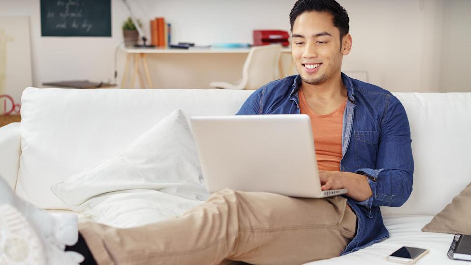 Young Asian man spending a relaxing day at home with his feet up on a sofa surfing the internet on a laptop computer with a smile, fees, America, money, payment, avoid fees, bills, debt