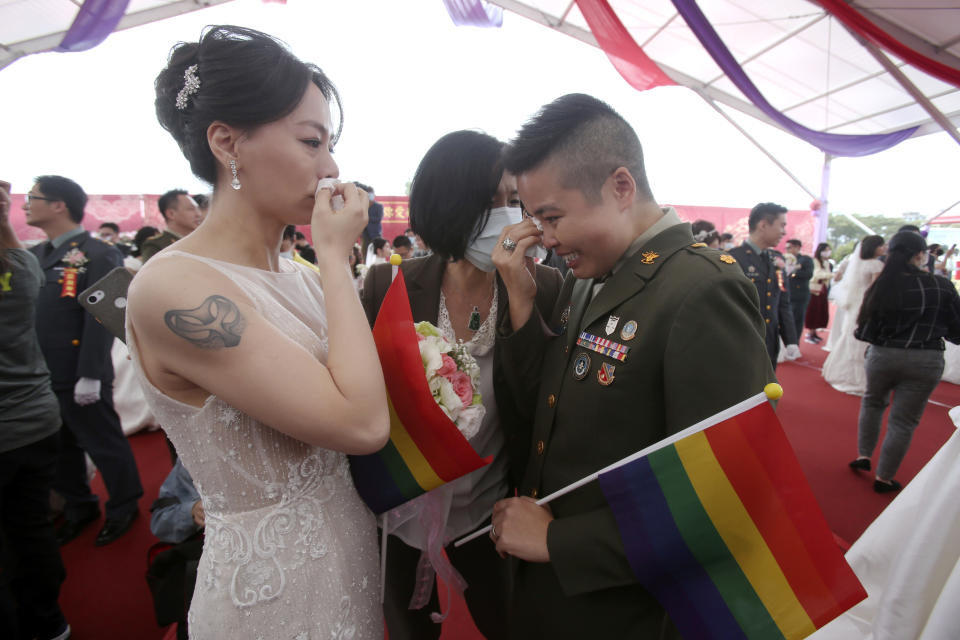 Lesbian couple Yi Wang, right, and Yumi Meng reacts for joy during a military mass weddings ceremony in Taoyuan city, northern Taiwan, Friday, Oct. 30, 2020. Two lesbian couples tied the knot in a mass ceremony held by Taiwan's military on Friday in a historic step for the island. Taiwan is the only place in Asia to have legalized gay marriage, passing legislation in this regard in May 2019. (AP Photo/Chiang Ying-ying)