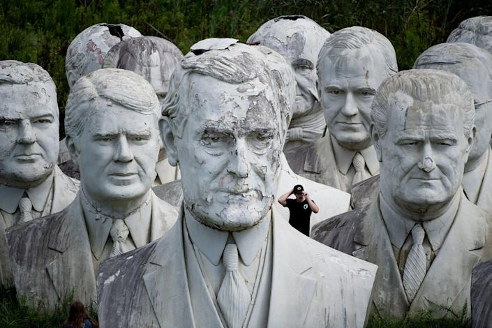 A man tours the salvaged bust of President Woodrow Wilson (front) and other busts of U.S. presidents at the mulching business where they now reside in Williamsburg, Va. (Photo: Brendan Smialowski/AFP/Getty Images)