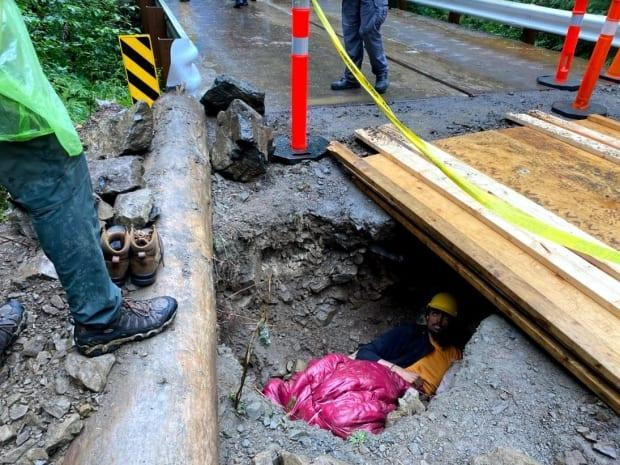 An old-growth logging demonstrator has secured himself in a trench that has been dug across the road at a blockade northeast of Port Renfrew, B.C. RCMP are attempting to extract him. (Adam van der Zwan / CBC - image credit)