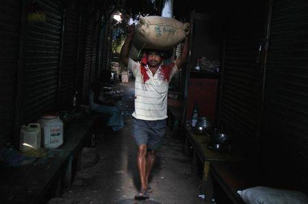 A labourer carries a sack filled with rice through an alley at a wholesale market in Kolkata March 14, 2014. REUTERS/Rupak De Chowdhuri/Files
