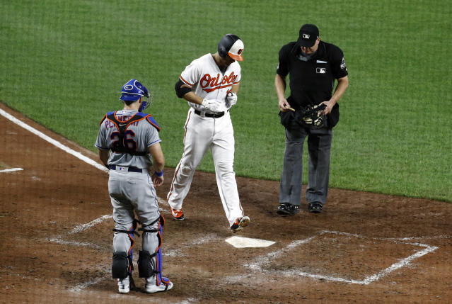 Baltimore Orioles' Chris Davis, center, crosses home plate in front of New York Mets catcher Kevin Plawecki, left, and umpire Jeff Nelson after rounding the bases on a solo home run in the seventh inning of a baseball game, Tuesday, Aug. 14, 2018, in Baltimore. (AP Photo/Patrick Semansky)