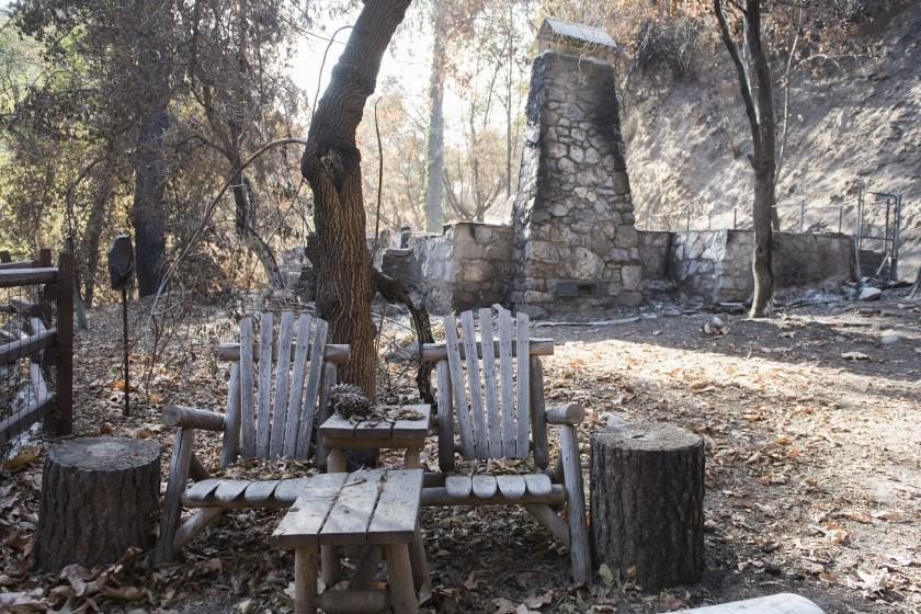 A pair of wooden chairs remain unscathed outside a historic cabin destroyed by the Bobcat Fire in Big Santa Anita Canyon in the Angeles National Forest on Saturday, Nov. 21, 2020. Seventeen historic cabins in the canyon were destroyed. ( Nick Agro / For The Times )