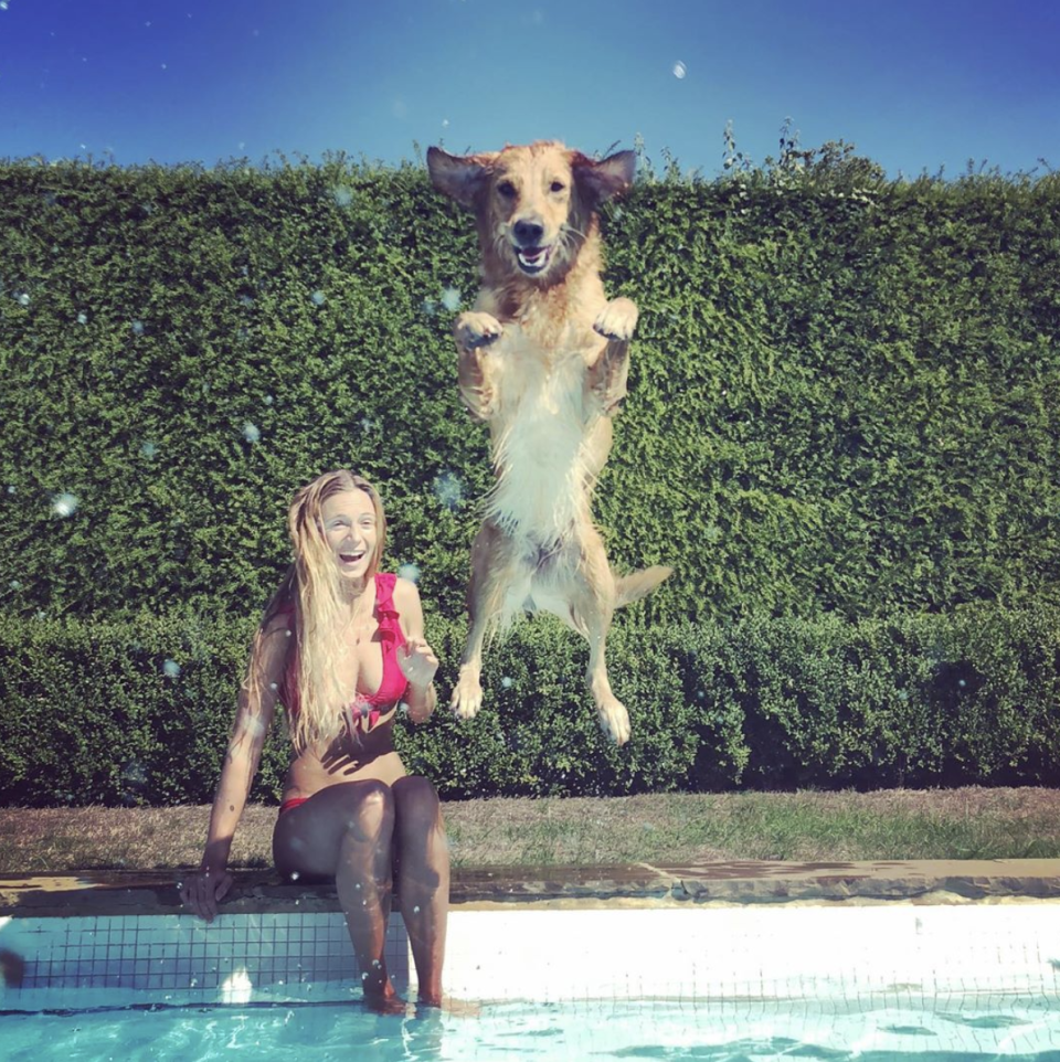 A photo of Alizée Thevenet wearing a red bikini sitting on the side of a pool as a dog leaps into the water