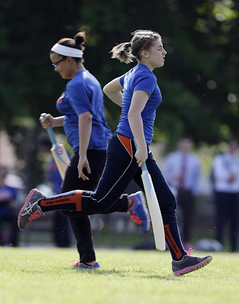 Jacqlynn Newsom, right, and Pandora Ward run between stumps during a cricket match Thursday, May 16, 2013, in Indianapolis. The Midwestern city best known for its basketball and auto racing is gearing up for a proper game of cricket ó the ball-and-bat sport most Americans know only from British films or by surfing through international sports channels. (AP Photo/Darron Cummings)