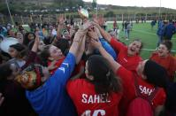 Women soccer team lift the trophy as they celebrate winning in an annual local soccer tournament, in the village of Sahel