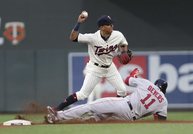 Minnesota Twins shortstop Ehire Adrianza turns a double play getting Boston Red Sox Rafael Devers (11) out at second in the fourth inning of a baseball game Wednesday, June 20, 2018, in Minneapolis. (AP Photo/Andy Clayton-King)
