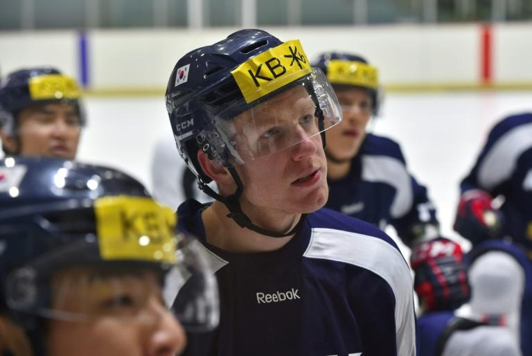 South Korea's ice hockey team player, Canada-born Eric Regan, listens to the coach Jim Paek during a practice session in Goyang, north-west of Seoul