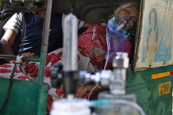 A COVID-19 patient breathes with the help of an oxygen mask and waits inside an auto rickshaw to be attended to and admitted to a dedicated COVID-19 government hospital in Ahmedabad, India, Saturday, April 17, 2021. Indian authorities scrambled Saturday to get oxygen tanks to hospitals where COVID-19 patients were suffocating amid the world's worst coronavirus surge, as the government came under increasing criticism for what doctors said was its negligence in the face of a foreseeable public health disaster. (AP Photo/Ajit Solanki)