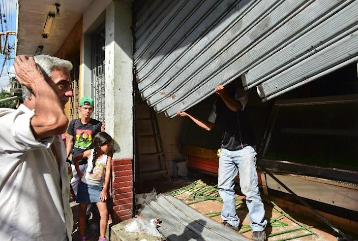A butcher and residents of the poor neighbourhood of Petare in Caracas, Venezuela, repair a butcher shop after it was looted on June 10, 2016 (AFP Photo/Ronaldo Schemidt)