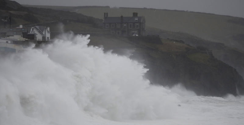 """Powerful waves break on the shoreline around the small port of Porthleven, south west England, Sunday, Feb. 16, 2020. Storm Dennis roared across Britain on Sunday, lashing towns and cities with high winds and dumping so much rain that authorities urged residents to protect themselves from """"life-threatening floods"""" in Wales and Scotland. (AP Photo/Alastair Grant)"""