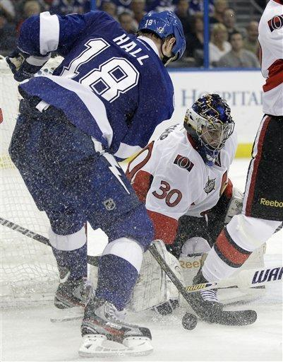 Ottawa Senators goalie Ben Bishop (30) makes a save on a shot by Tampa Bay Lightning right wing Adam Hall (18) during the second period of an NHL hockey game Tuesday, March 6, 2012, in Tampa, Fla. (AP Photo/Chris O'Meara)