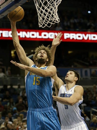 New Orleans Hornets' Robin Lopez (15) gets off a shot in front of Orlando Magic's Nikola Vucevic (9), of Montenegro, during the first half of an NBA basketball game on Wednesday, Dec. 26, 2012, in Orlando, Fla. (AP Photo/John Raoux)