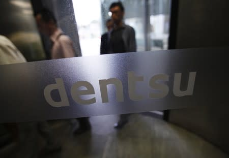FILE PHOTO:  The logo of Dentsu Co. is seen at the entrance of the company headquarters in Tokyo