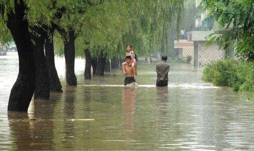 People walk down a flooded road in Anju city in North Korea's South Phongan province