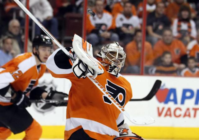 Philadelphia Flyers goalie Ray Emery deflects the puck over his head during the first period of an NHL hockey game against the Calgary Flames, Saturday, Feb. 8, 2014, in Philadelphia. (AP Photo/Tom Mihalek)
