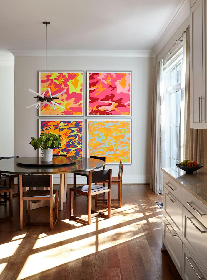 """Four Andy Warhol screen prints, from a series called <em>Camouflage,</em> hang in the dining area of the kitchen. The resin-topped pedestal table, with a custom lazy Susan, is from <a href=""""https://wudfurniture.com/product_type/furniture/"""" rel=""""nofollow noopener"""" target=""""_blank"""" data-ylk=""""slk:Wüd"""" class=""""link rapid-noclick-resp"""">Wüd</a>, and the leather-backed chairs are from <a href=""""http://bddw.com/furniture/seating/dining_chairs/square_guest_chair"""" rel=""""nofollow noopener"""" target=""""_blank"""" data-ylk=""""slk:BDDW"""" class=""""link rapid-noclick-resp"""">BDDW</a>."""