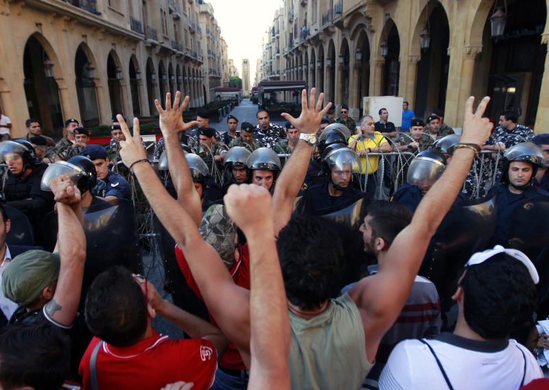 Civil society protesters chant slogans against Lebanese lawmakers during a demonstration protesting the extension of parliament's mandate, near Parliament in Beirut, Lebanon, Friday, June 21, 2013. Lebanon's parliament on May 29 extended its term by a year and a half, skipping scheduled elections because of the country's deteriorating security linked to the civil war next door in Syria. (AP Photo/Bilal Hussein)