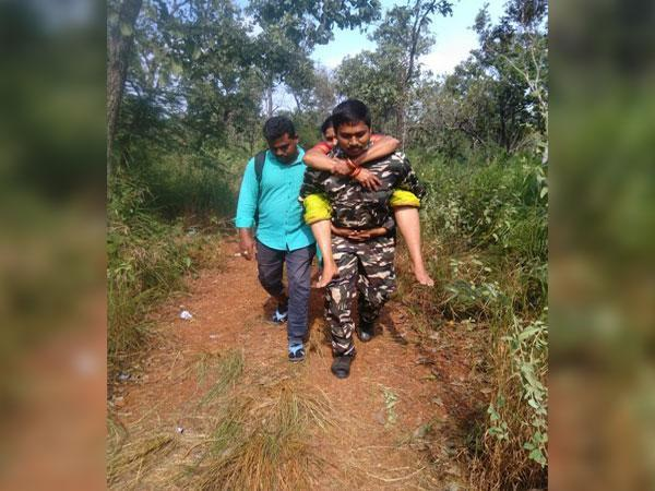 A visual of the constable carrying the woman on way to Tirumala temple in Andhra Pradesh.