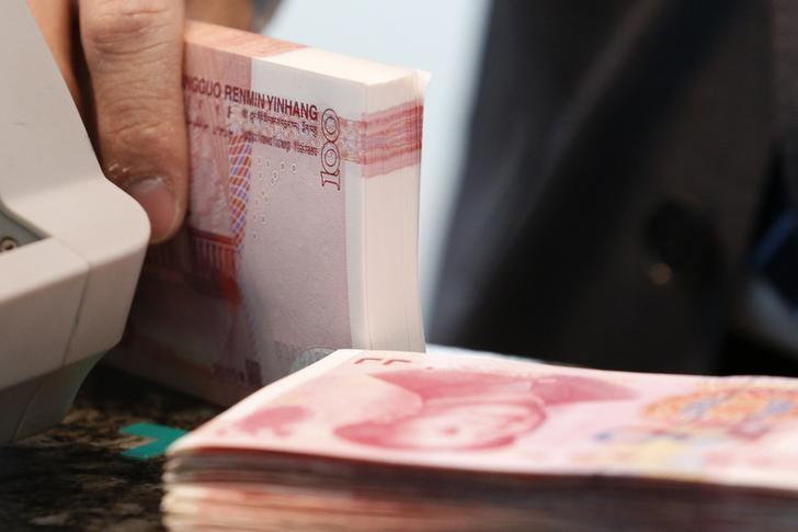 A bank clerk holds Chinese 100 yuan banknotes at a branch of a commercial bank in Beijing