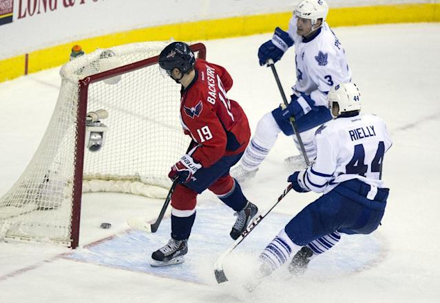 Washington Capitals center Nicklas Backstrom (19) skates past Toronto Maple Leafs defenseman Dion Phaneuf (3) and defenseman Morgan Rielly (44) to watch an empty net goal shot by right wing Troy Brouwer go into the goal to seal the game during the third period of an NHL hockey game on Sunday, March 16, 2014, in Washington. The Capitals won 4-2. (AP Photo/ Evan Vucci)