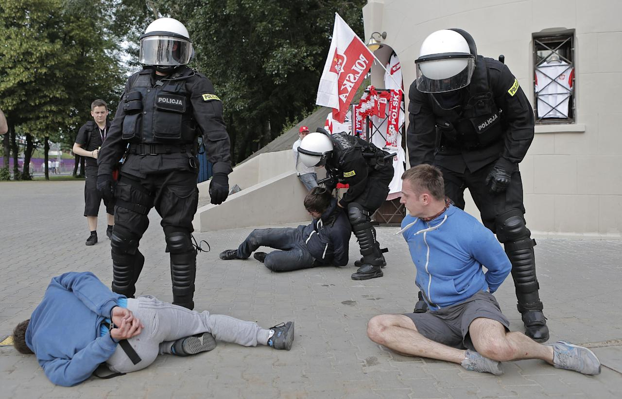 Police arrest soccer fans prior to the Euro 2012 soccer championship Group A match between Poland and Russia in Warsaw, Poland, Tuesday, June 12, 2012. Russian soccer fans clashed with police and Poland supporters in separate incidents in Warsaw on Tuesday, just hours before the two teams were to meet in an emotionally charged European Championship match. Several people were injured. (AP Photo/Gero Breloer)