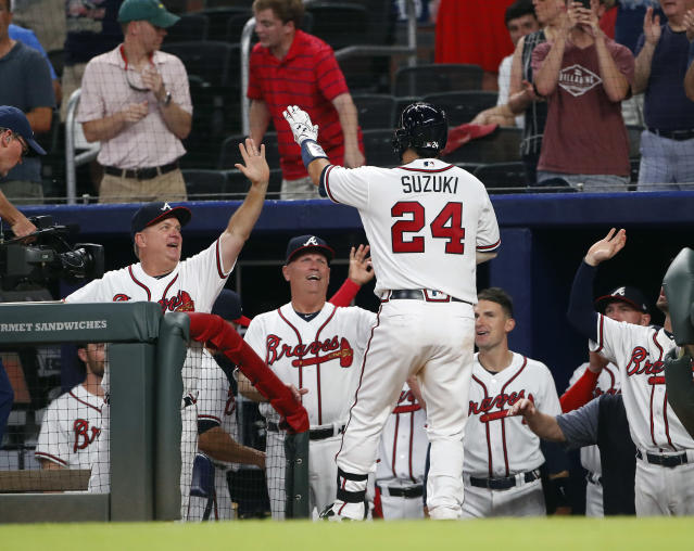 Atlanta Braves' Kurt Suzuki (24) is greeted at the dugout by hitting coach Kevin Seitzer, left, and manager Brian Snitker after hitting a home run during the seventh inning of the team's baseball game against the Miami Marlins on Saturday, May 19, 2018, in Atlanta. (AP Photo/John Bazemore)